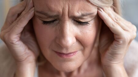 Upset stressed middle aged old woman feel pain in sore head terrible migraine, sad tired senior middle aged lady suffer from mental problem, panic attack having strong headache concept, close up view Stock Photo