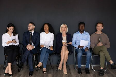 Serious stressed diverse young and old applicants business people rivals group sit on chairs wait prepare for hr job interview sit in row queue, human resource, recruit staffing employment concept