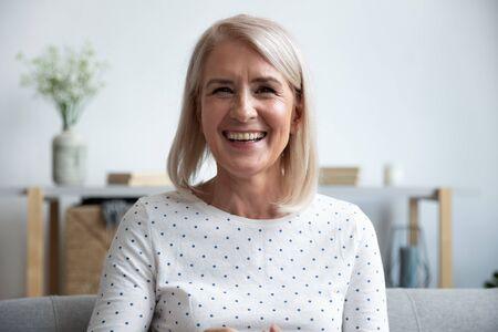 Szczęśliwa dojrzała starsza kobieta blogerka patrząca na kamerę w domu, uśmiechnięta starsza pani w średnim wieku siedzi na kanapie rozmawiając przez kamerę internetową, śmiejąc się, ciesząc się wideokonferencją online lub kręcąc blog na blogu w domu