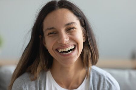 Close up head shot portrait smiling pretty millennial mixed race young girl feeling rejoice. Happy positive attractive young woman laughing, having fun, hearing good news, looking at camera. Stok Fotoğraf