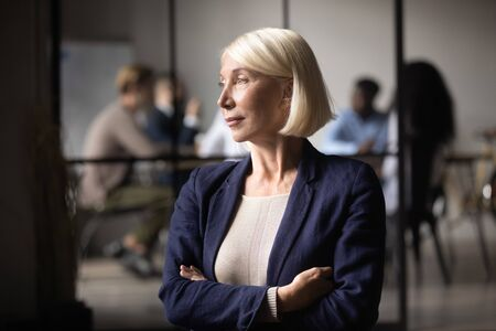 Thoughtful successful middle aged old businesswoman executive ceo standing looking through window thinking of leadership opportunities, business vision success, dreaming planning future concept