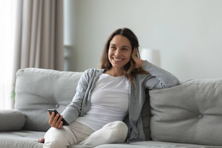 Happy millennial mixed race woman sitting on cozy sofa with smartphone in hands, received pleasant sms or good news notification. Smiling sincere young girl feeling positive emotions at home.