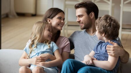 Happy parents with little daughter and son sitting on couch, looking at each other, enjoying tender moment together, children sitting on smiling mum and dad lap, cuddling, expressing love and unity