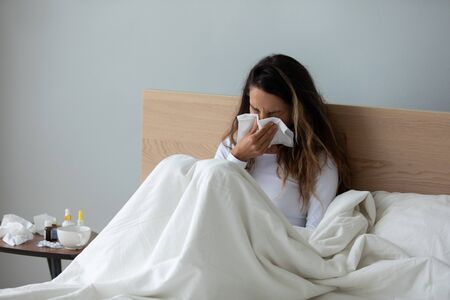 Unhealthy millennial mixed race girl sitting under duvet on bed, using paper tissue, suffering from runny nose. Young biracial woman feeling unwell, caught cold, treating independently at home.