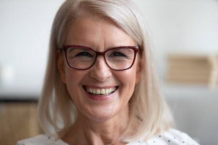 Happy older mature woman cheerful face healthy teeth wearing glasses looking at camera at home, smiling positive beautiful adult middle aged senior lady laughing posing for close up portrait Stok Fotoğraf