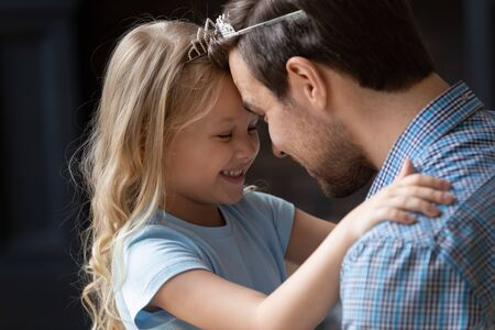 Close up adorable little daughter and father wearing princess crown touching foreheads, enjoying tender moment, expressing love and care, smiling cute girl hugging dad, good family relations