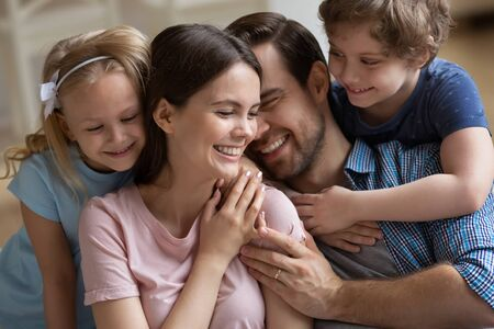 Happy family enjoying tender moment, parents and children hugging close up, smiling mother, father and cute little daughter and son cuddling, having fun, congratulating mum with mothers day