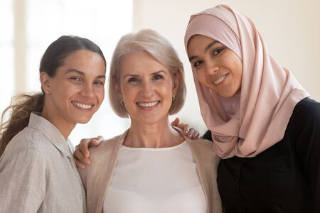 Three happy beautiful diverse two generation women young asian muslim woman wear hijab and caucasian older mature female multicultural ladies bonding standing together looking at camera, portrait Stockfoto