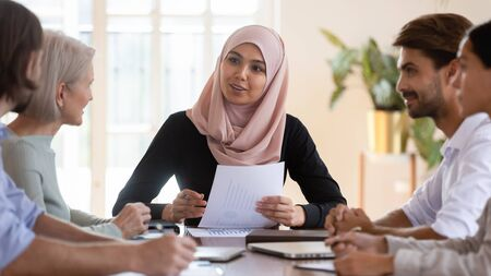 Young asian muslim businesswoman executive wear hijab discussing paperwork financial results consult clients employees group explain project plan at corporate briefing sit at company meeting table