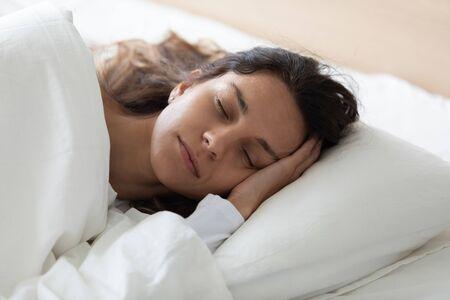 머리에 총을 맞은 고요한 젊은 혼혈 여성이 침대에 누워 있고 신선한 린넨으로 덮여 있으며 게으른 주말 시간을 즐기고 있습니다. 집에서 평화로운 느낌, 닫힌된 눈으로 편안한 예쁜 여자.