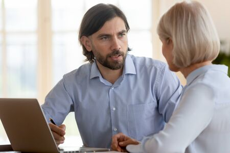 Male broker insurer manager consulting female middle aged old client explaining insurance services deal benefit make business offer to customer, mentor teaching mature worker at office meeting course