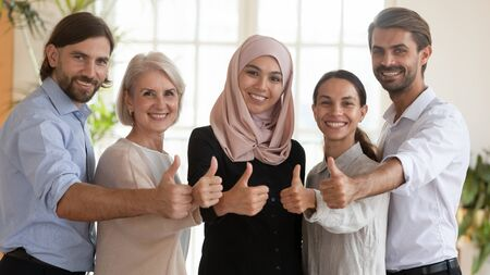 Happy proud multicultural business team people show thumbs up looking at camera, smiling professional corporate staff group asian muslim and caucasian employees stand together human resource portrait 版權商用圖片