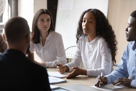 Young african businesswoman mentor teaching multiracial people during group briefing, female leader manager training diverse corporate business team explaining project plan at office table meeting