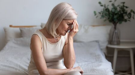 Sick older mature woman sit on bed feel pain dizziness coping with morning headache concept, upset tired middle aged adult woman touching sore head suffer from terrible migraine mental problem Stock Photo