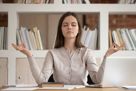 Serene student girl seated at desk distracted from study process learning exams preparations closed eyes reduces tiredness doing no stress exercise yoga practice reaching harmony inner balance concept.