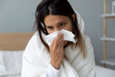 Head shot close up unhealthy millennial mixed race girl sitting on bed, covered with blanket, using paper handkerchief, wiping runny nose. Unhappy woman suffering from grippe, treating at home.