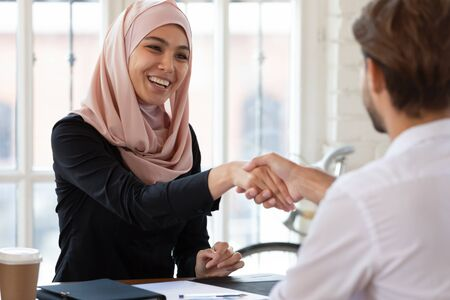 Happy asian muslim businesswoman hr manager employer wear hijab handshake hire male applicant make contract deal with partner collaborate shake client hand at job interview business meeting concept Zdjęcie Seryjne - 132247391