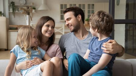 Smiling mother and father with kids sitting on couch, looking at each other, enjoying tender moment together, little children sitting on happy mum and dad lap, cuddling, expressing love and unity Reklamní fotografie