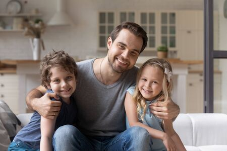 Portrait smiling father with adorable son and daughter sitting on comfortable couch at home, caring dad hugging little kids, looking at camera, family posing for picture together, having fun Reklamní fotografie