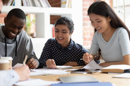 Multi-ethnic students do school assignment together sitting at desk in modern classroom, indian, african, asian classmates using compendium make home work, prepare for exams, studying process concept