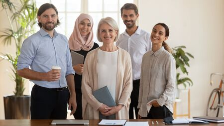Happy young multicultural office team people and middle aged old company ceo leader boss stand together look at camera, smiling confident diverse professional employees staff group corporate portrait