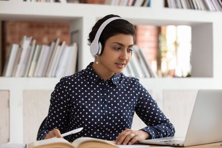 Attractive indian ethnicity girl do assignment preparing for university test or exams seated at desk in public library wearing headphones listen audio task, e-learning process educational app concept
