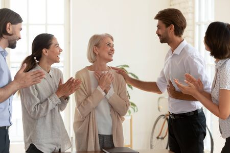 Happy grateful old middle aged female employee get promoted rewarded by boss and multiethnic team appreciate best mature worker applaud praise senior businesswoman standing in office, respect concept
