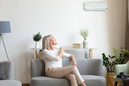Mujer feliz de mediana edad sosteniendo el interruptor de control remoto del clima en el aire acondicionado en la pared, sentarse en el sofá en la sala de estar, disfrutar del sistema de aire acondicionado fresco en una cómoda casa moderna, relajarse en el sofá Foto de archivo