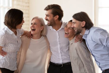 Cheerful multiethnic business team people laughing bonding standing in office, friendly happy diverse colleagues employees embracing celebrate corporate success having fun at staff party concept Imagens