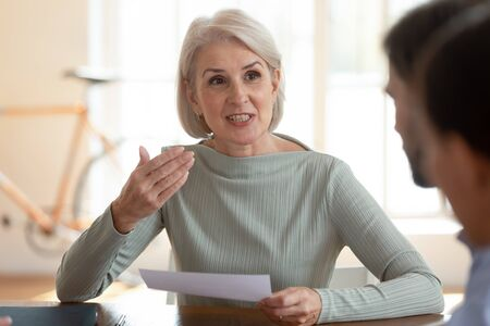Confident older mature businesswoman mentor coach negotiator or job applicant speak at business negotiations interview, old female manager executive hold paper consult clients at office meeting table