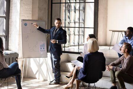 Hombre serio, conferenciante, entrenador, presentador, gerente, traje, presentación de negocios corporativos, dibujo en rotafolio, explicación de estrategia financiera, capacitación de diversos grupos de personas en la oficina moderna Foto de archivo