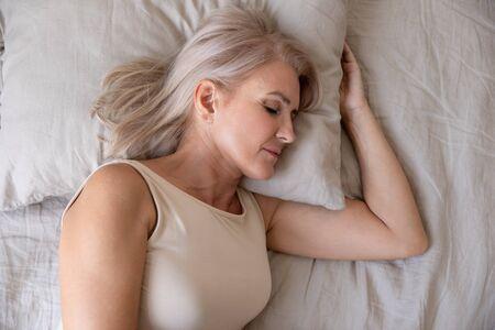 Friedliche, gesunde, schöne 50er Jahre reife Frau, die auf bequemen Kissen liegt, orthopädische Matratze, die gut in einem gemütlichen Bett allein schläft, ruhige, ruhige alte Frau, die im Schlafzimmer ruht, Nahaufnahme von oben