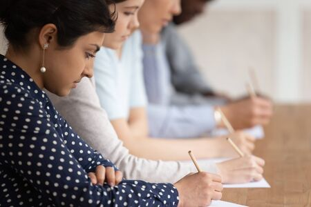Multinational students seated at desk in row holding pencils writing on papers, take part in university exams, learning process or test of scholars knowledge skill in subject, higher education concept Archivio Fotografico