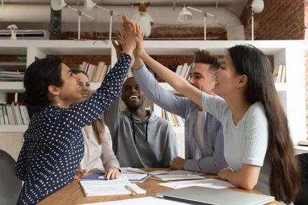 Un groupe d'étudiants d'amis multiethniques s'assoit au bureau pour célébrer l'obtention du diplôme ou les réalisations de l'équipe.