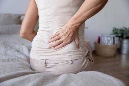 Oude volwassen vrouw zit op bed raak rug aan voel ochtendrugpijn lijdt aan lagere lumbale ongemakken spierpijn wakker worden met rugpijn na slaap op ongemakkelijk matrasconcept, close-up achteraanzicht