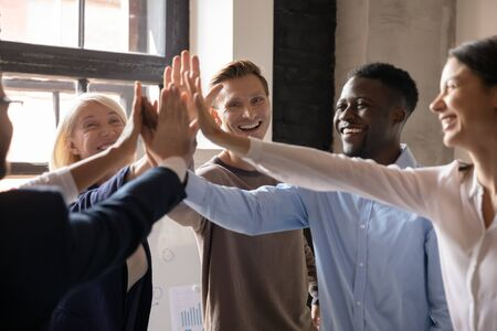 Motivated diverse business office professional team young and old employees group give high five together promise unity support in teamwork engaged in partnership celebrate corporate success concept