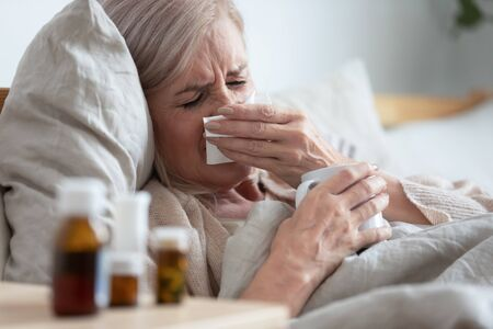 Ill sick middle aged woman sneezing blowing running nose holding tissue sit on bed, upset old mature lady caught cold got flu influenza grippe symptoms drink hot tea taking medications at home alone Stock Photo