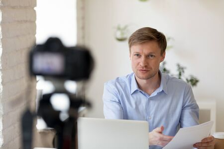 Serious confident young professional lecturer coach mentor speaker sitting at desk with computer in front of camera, recording educational lecture for personal channel, presenting financial report.