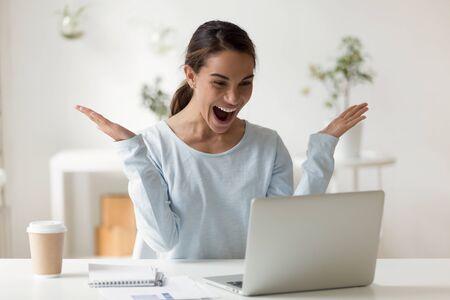 Kopfschuss Nahaufnahme Porträt überglücklich überrascht junge gemischte Geschäftsfrau erhielt E-Mail mit guten Nachrichten. Überraschte Start-up-Unternehmerin feiert unglaublichen Erfolg, Lotteriegewinn.