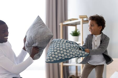 Excited african American young father play go crazy with cute little biracial son in bedroom, smiling overjoyed mixed race dad have fun with small boy child, involved in pillow fight at home