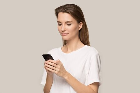Beautiful young Caucasian woman in white t-shirt isolated on grey studio background using modern smartphone application, millennial girl browsing wireless unlimited internet fast connection on cell 版權商用圖片