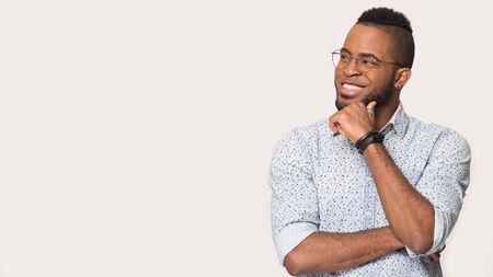 Sorridente uomo afroamericano con gli occhiali isolati su sfondo grigio studio guarda lo spazio vuoto della copia spazio pubblicitario vacante pensando, maschio biraziale felice con gli occhiali che riflette su una buona offerta di vendita