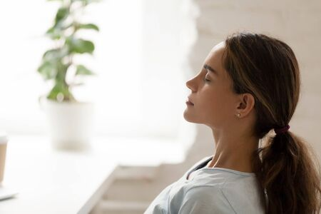 Side view young mixed race woman relaxing with closed eyes at workplace. Peaceful biracial lady freelancer deeply meditating, doing breathing exercises, enjoying break time, reducing stress at office.