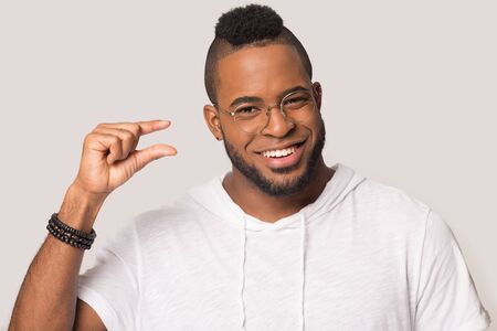 Headshot of smiling african American man in glasses isolated on grey studio background look at camera show small measurement with hands, happy biracial male demonstrate tiny little prices gesture Imagens