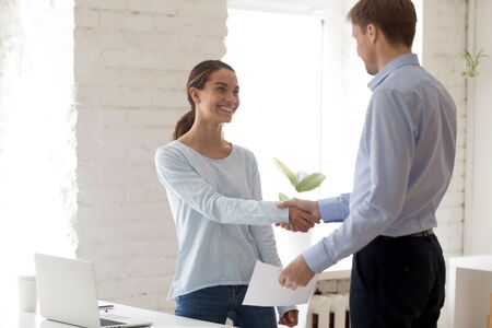 Confident middle aged male boss shaking hands with happy young mixed race female intern employee, holding envelope with money reward, congratulating with good work results, encouraging coworker.