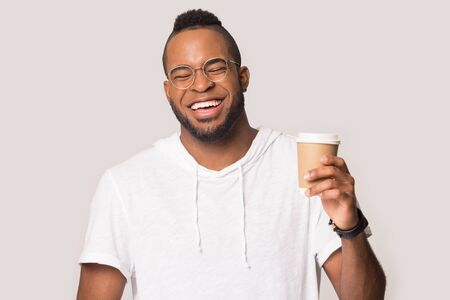 Overjoyed african American millennial man in glasses isolated on grey studio background hold takeaway coffee cup recommend coffee shop, happy biracial male client smile enjoy hot drink from café Stockfoto