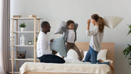 Excited multiracial young family with little boy child have fun in bedroom engaged in pillow fight, overjoyed happy international mom and dad play with small son, enjoy weekend at home together