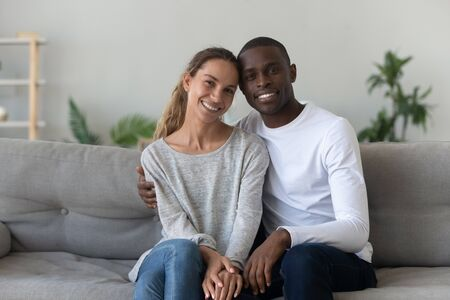 Portrait of smiling interracial millennial husband and wife sit on couch at home posing for picture together, happy multiethnic lovers look at camera hug embrace on sofa, show love and affection