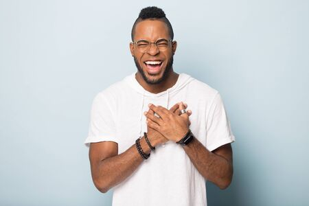 Excited biracial male in spectacles and sportswear isolated on blue studio background keep hands at heard chest feel happy, smiling african American man believer laugh thanking, faith concept Imagens