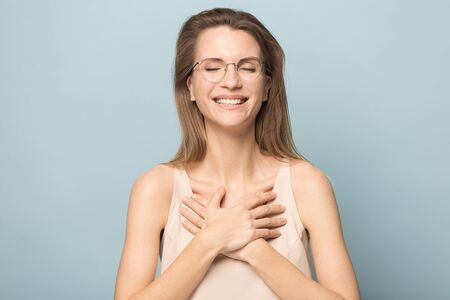 Happy calm millennial woman in spectacles isolated on blue studio background hold hands at heart chest feel thankful, grateful young Caucasian female in glasses thanking smiling, relieve negativity 版權商用圖片 - 132348247